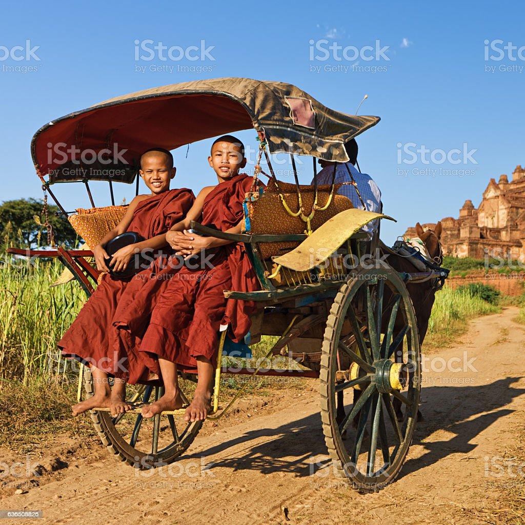 Two young Buddhist monks on the horse cart in Bagan stock photo