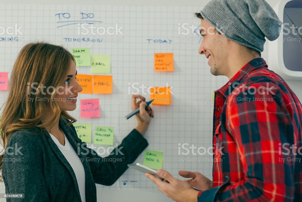 Two Young Business People Standing and Brainstorming. stock photo