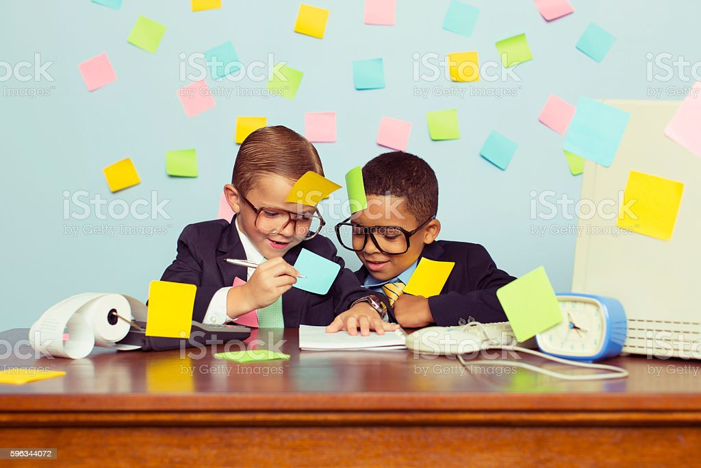 Two Young Businessmen at Desk Covered with Sticky Notes stock photo