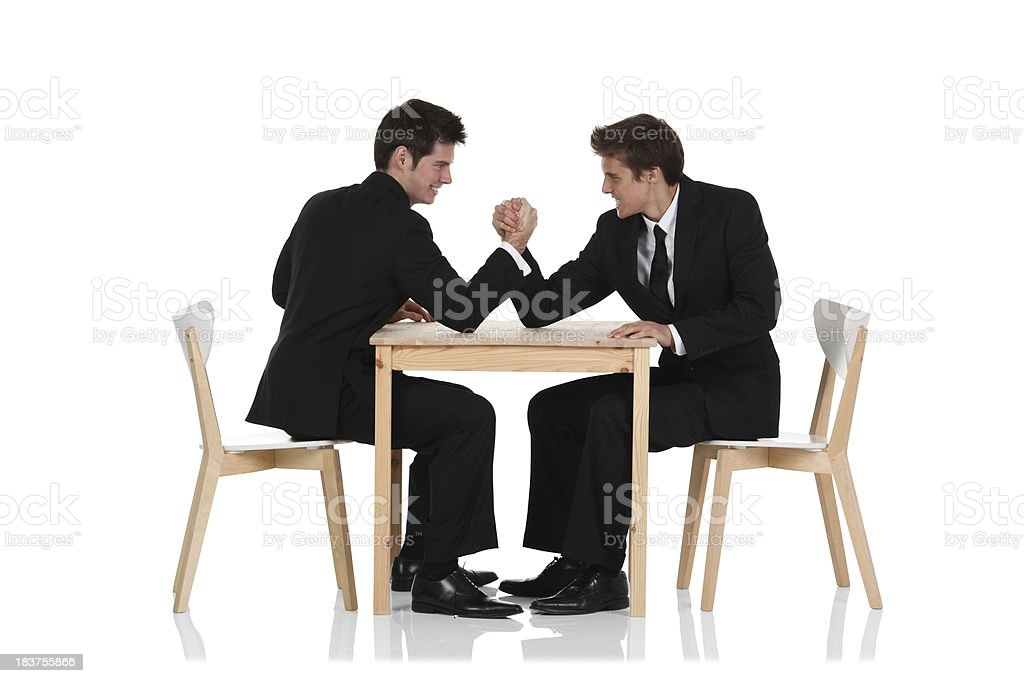 Two young businessmen having an arm wrestle royalty-free stock photo