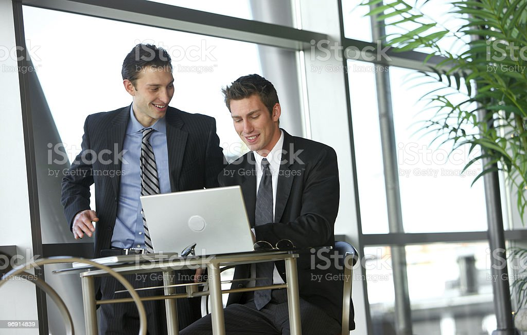 Two young businessmen look at laptop royalty-free stock photo