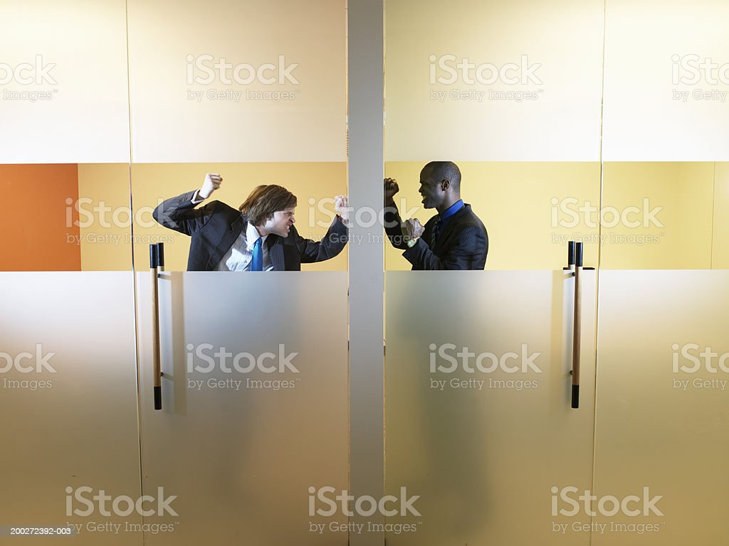 Two young businessmen making fists at wall, view through window stock photo