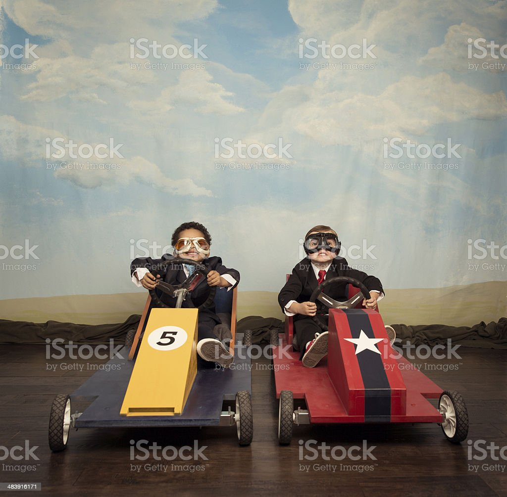 Two young businessmen race each other in toy cars stock photo