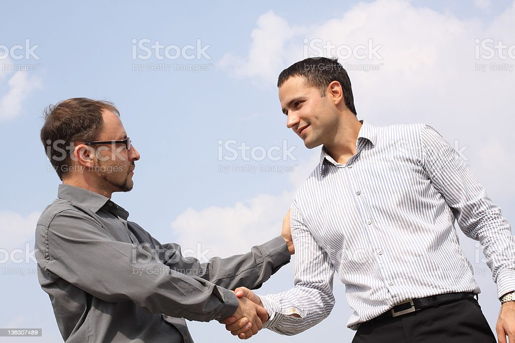 Two young businessmen shaking hands royalty-free stock photo