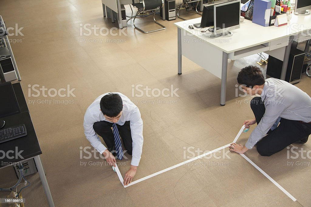 Two young businessmen taping up the floor royalty-free stock photo