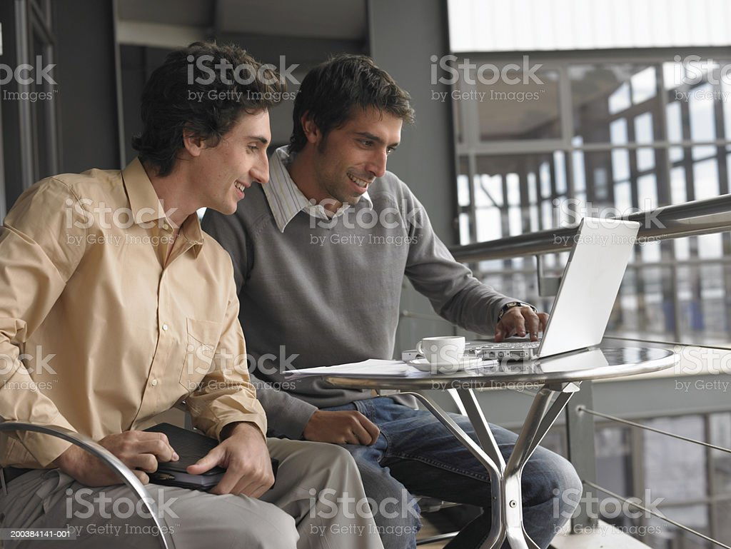 Two young businessmen using laptop sitting at table royalty-free stock photo
