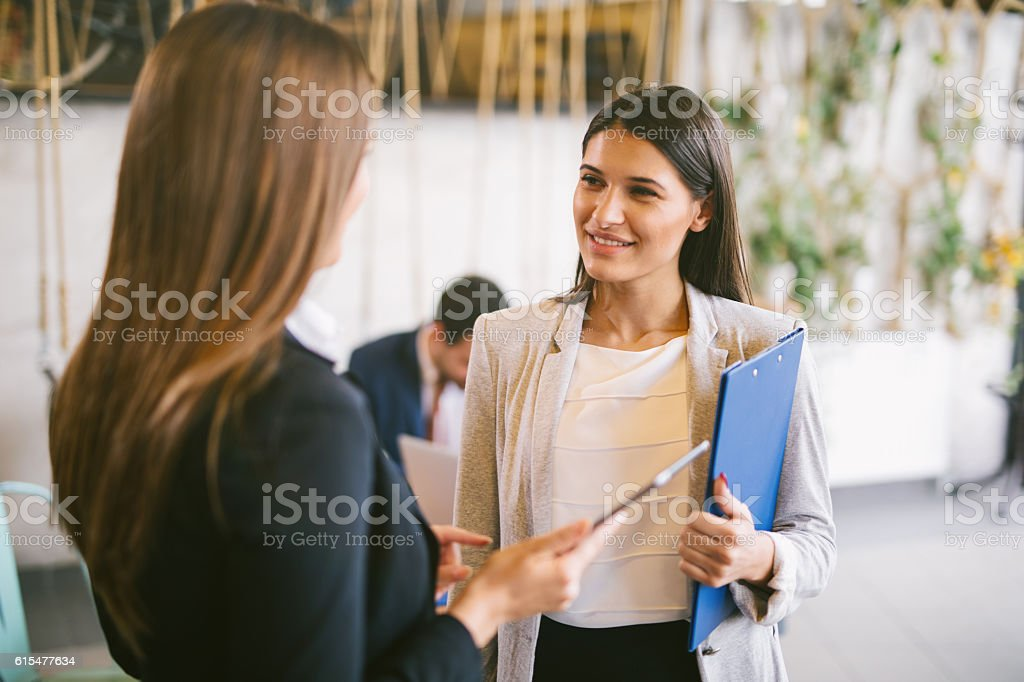 Two young businesswomen discussing business strategy using digital tablet stock photo