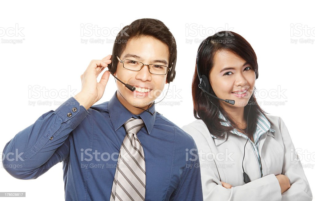Two young call center workers saying how can we help you stock photo