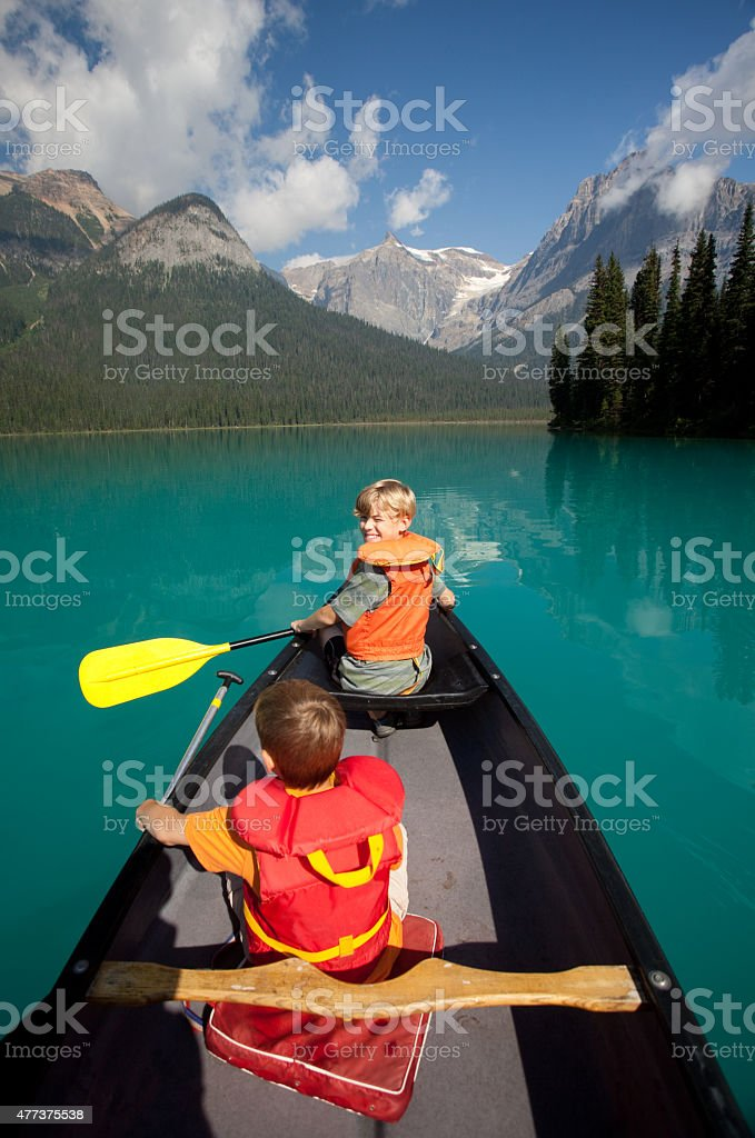 Two Young Caucasian Boys Paddling a Canoe in Canadian Rockies stock photo