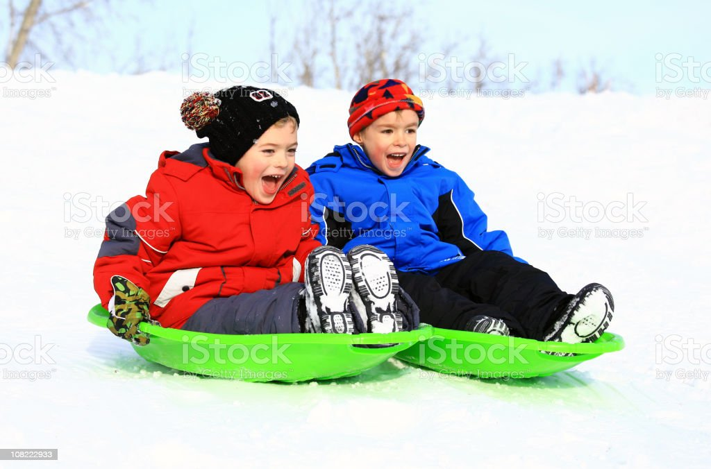 Two Young Caucasian Boys Sledding in Winter Snow stock photo