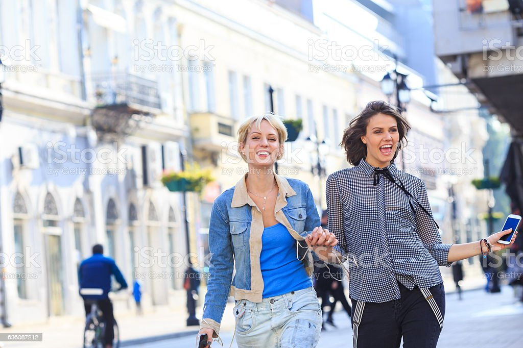Two young cheerful women walking on street and holding hands stock photo