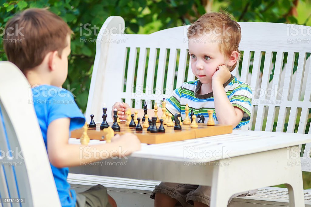 two young chess players outdoors stock photo