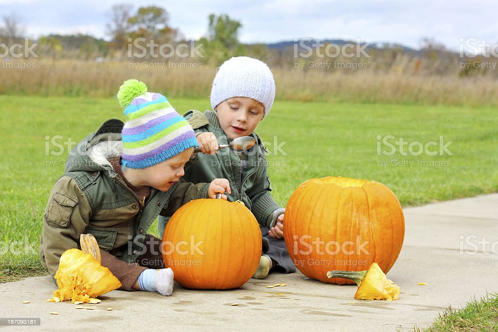 Two Young Children Carving Pumpkins royalty-free stock photo