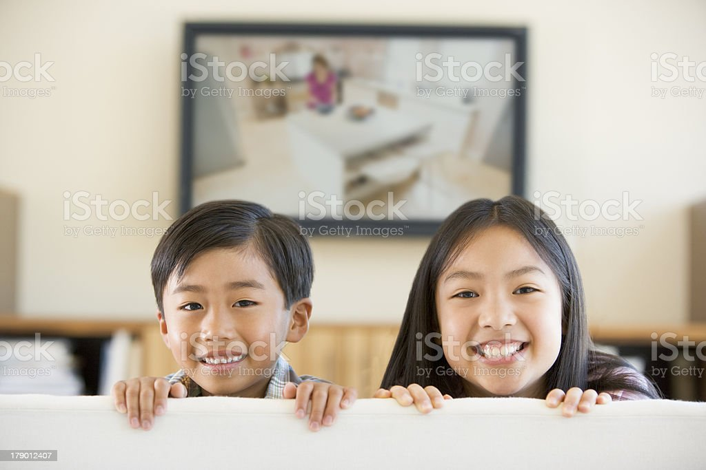 Two young children in living room with flat screen television royalty-free stock photo
