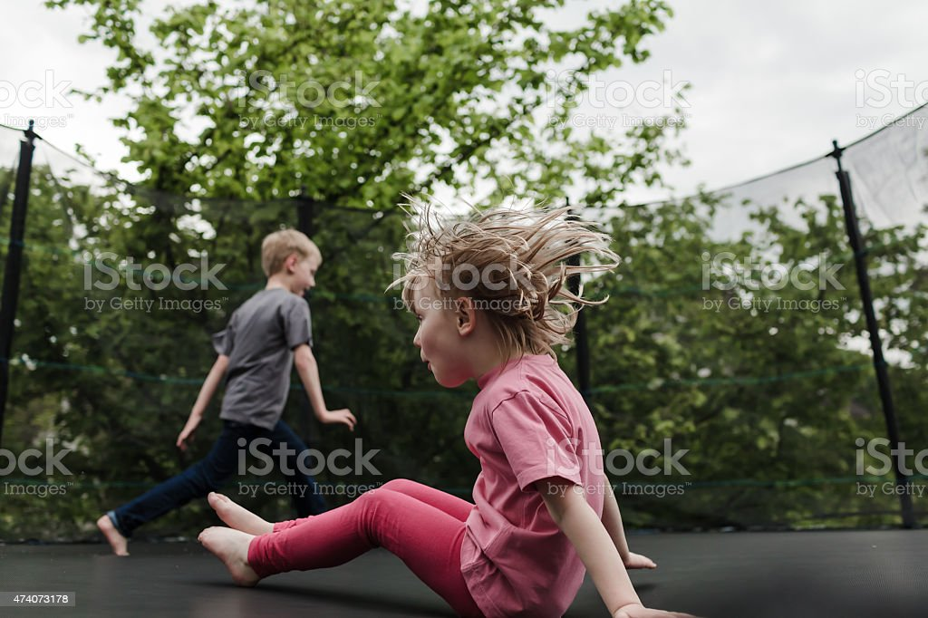 Two young children playing on a trampoline stock photo