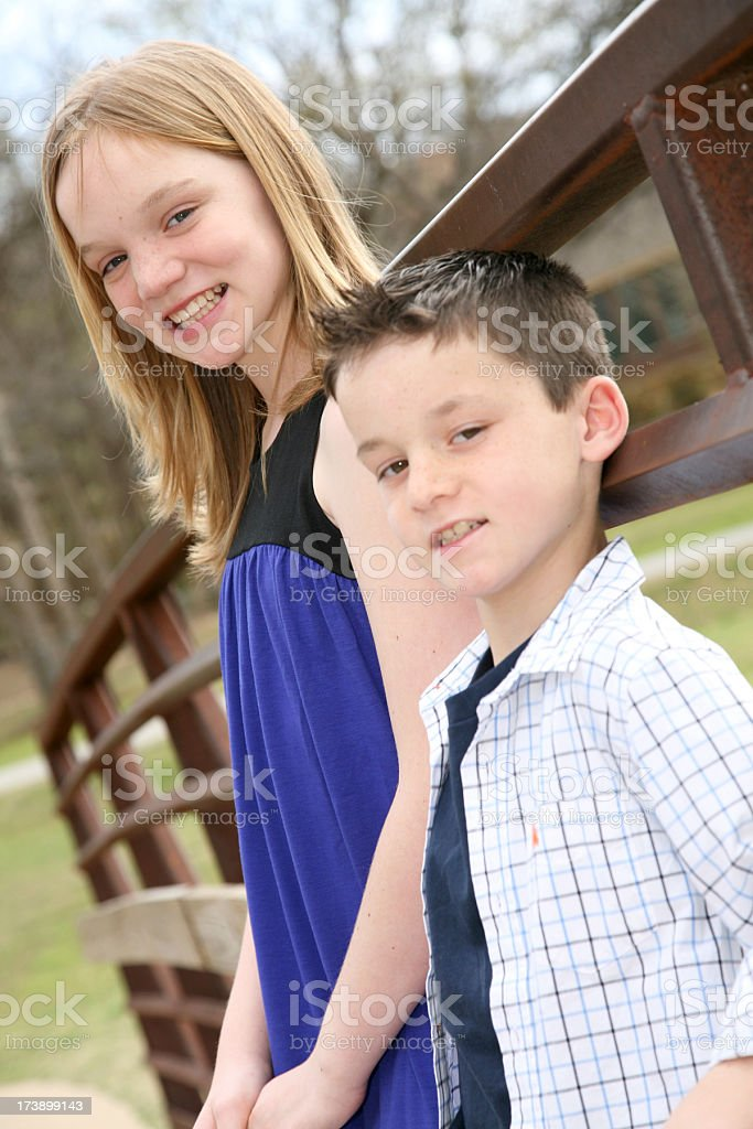 two young children smiling whilst having fun at the park royalty-free stock photo