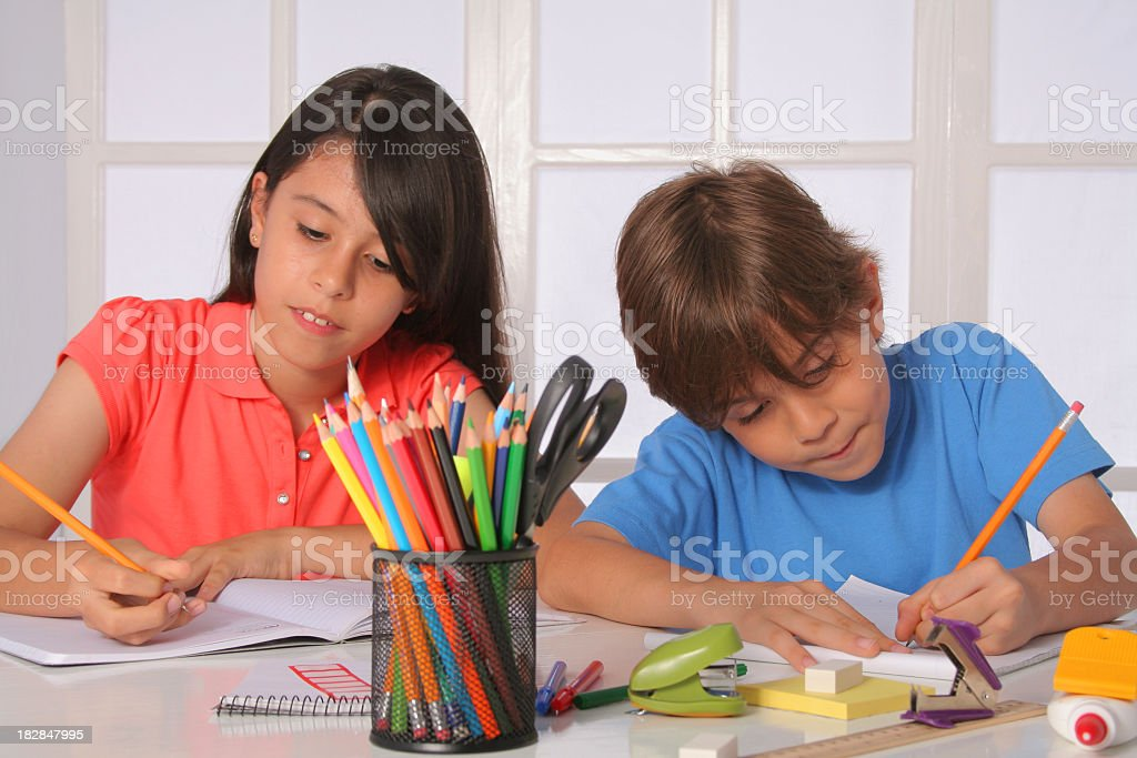Two young children working at a table with various art items royalty-free stock photo