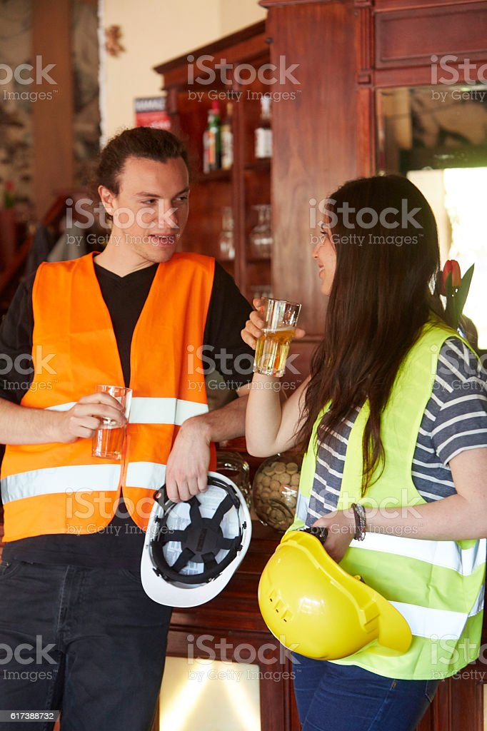 Two young civil engineers drinking beer during work break. Vertical stock photo
