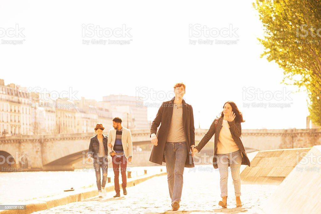 Two Young Couples Walking Along the Seine in Paris France stock photo