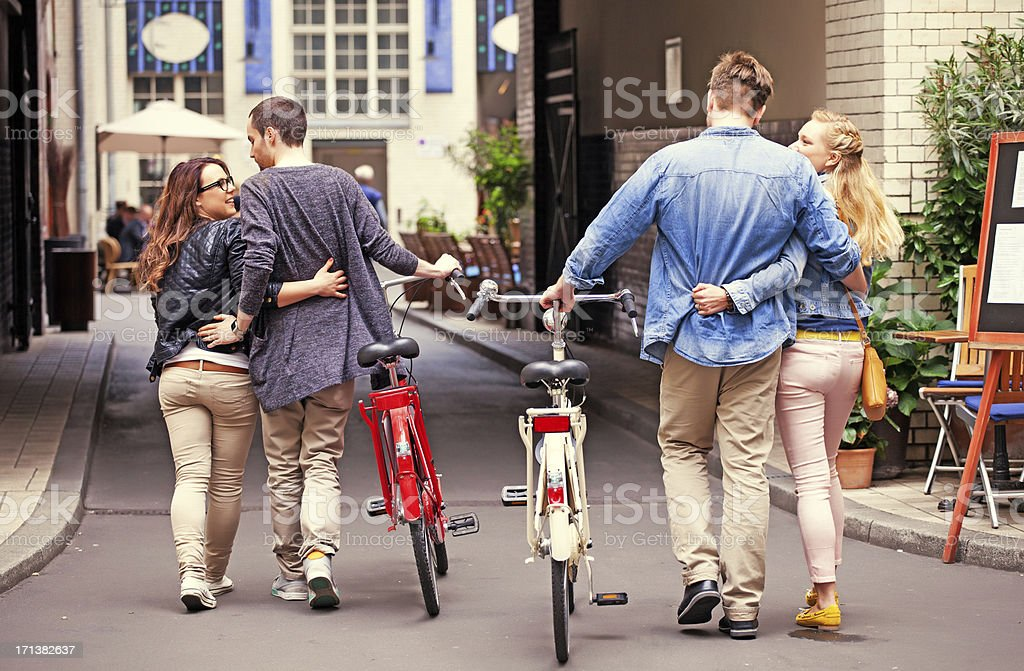 two young couples walking at city, guys holding bikes stock photo