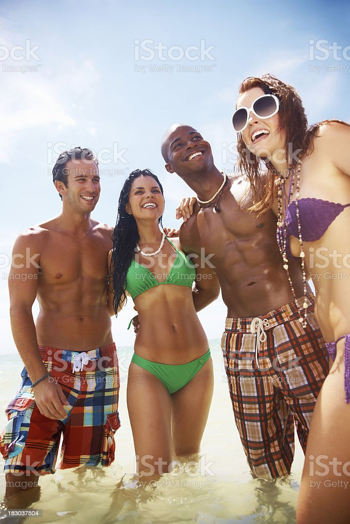 Two young couples with arms around enjoying their vacation royalty-free stock photo
