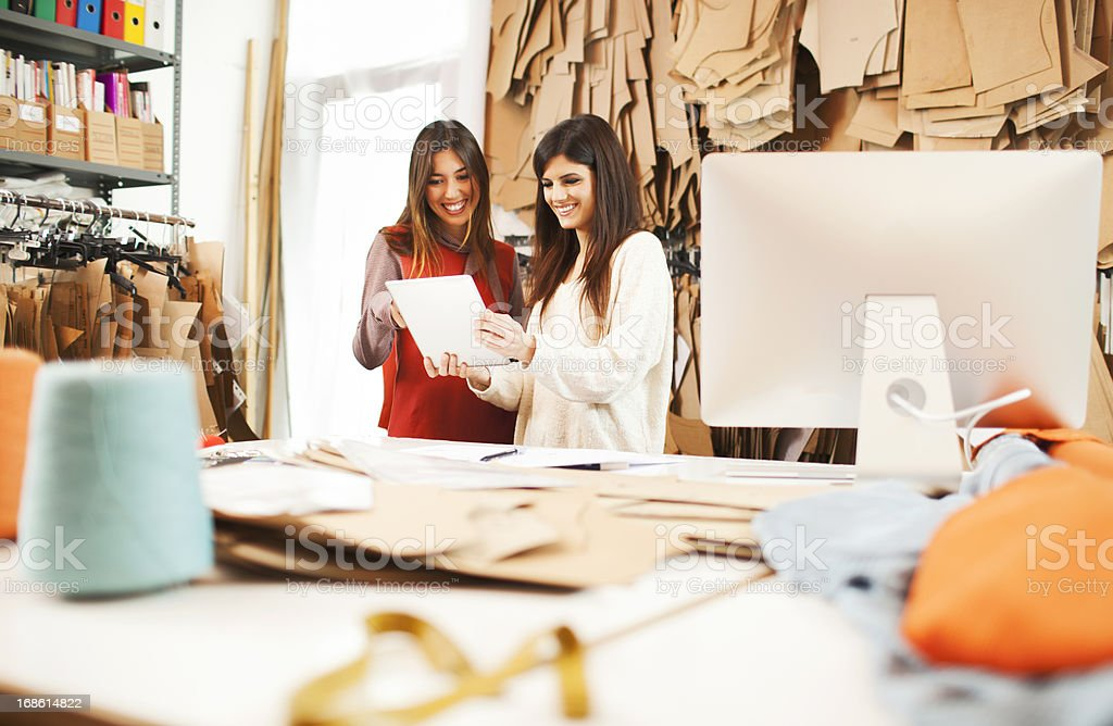 Two young designers brainstroming on digital tablet. stock photo