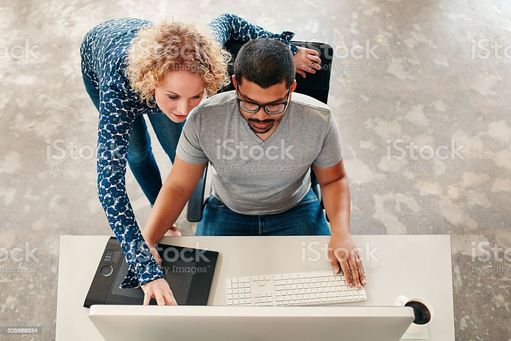 Two young designers working on a pc stock photo