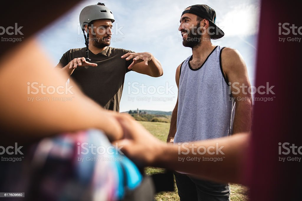 Two young extreme sportsmen discussing in nature. stock photo
