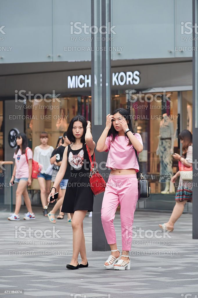Two young, fashionable girls at Beijing The Village shopping area. stock photo
