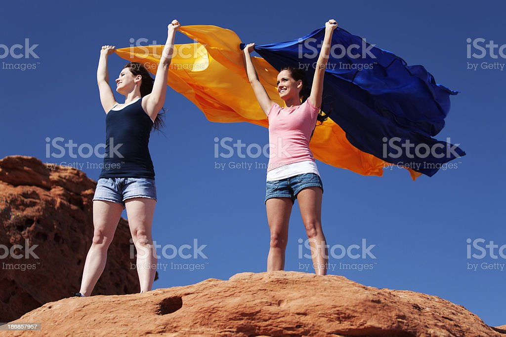 Two young female adults holding fabric into the wind stock photo