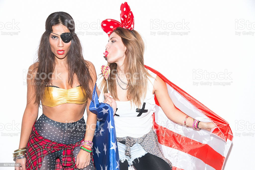 Two young female friends having fun on costume ball stock photo