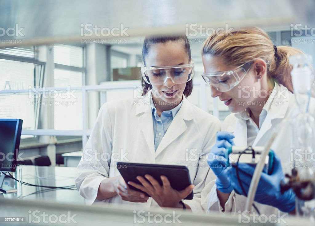 Two Young Female Scientists Looking at the PC tablet stock photo