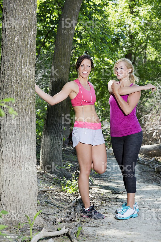 Two young fit women stretching before the run on trail royalty-free stock photo