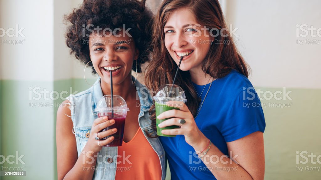 Two young friends drinking fresh fruit juice stock photo