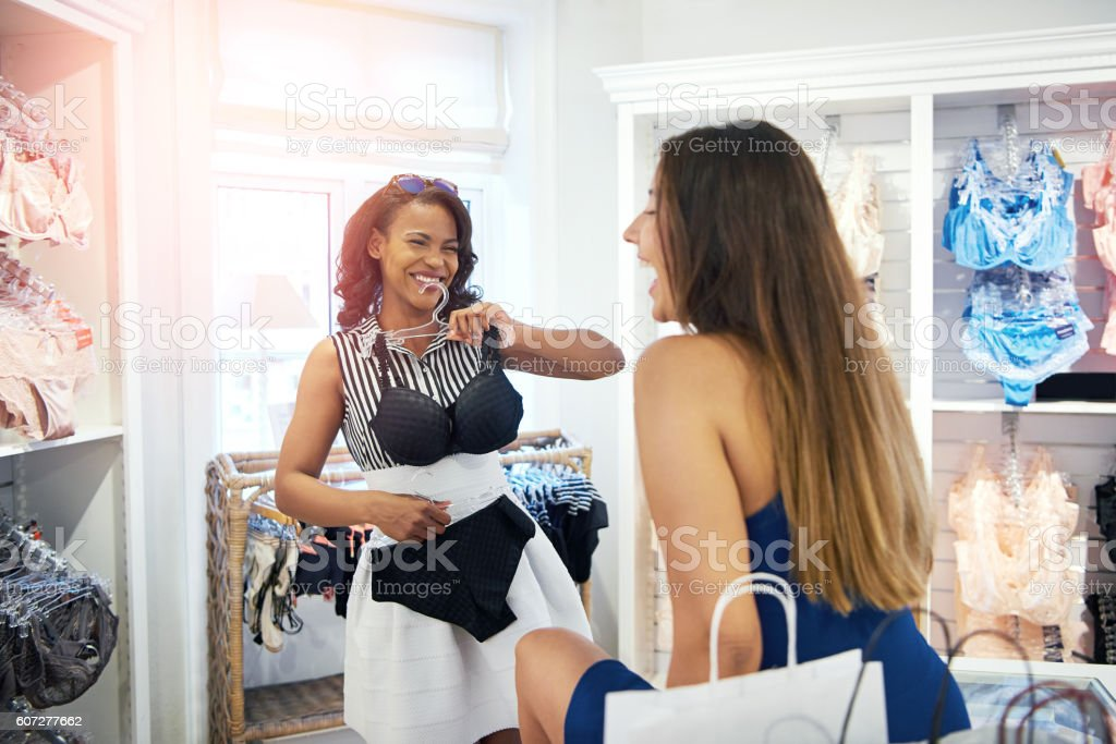 Two young friends laughing in a clothing store stock photo
