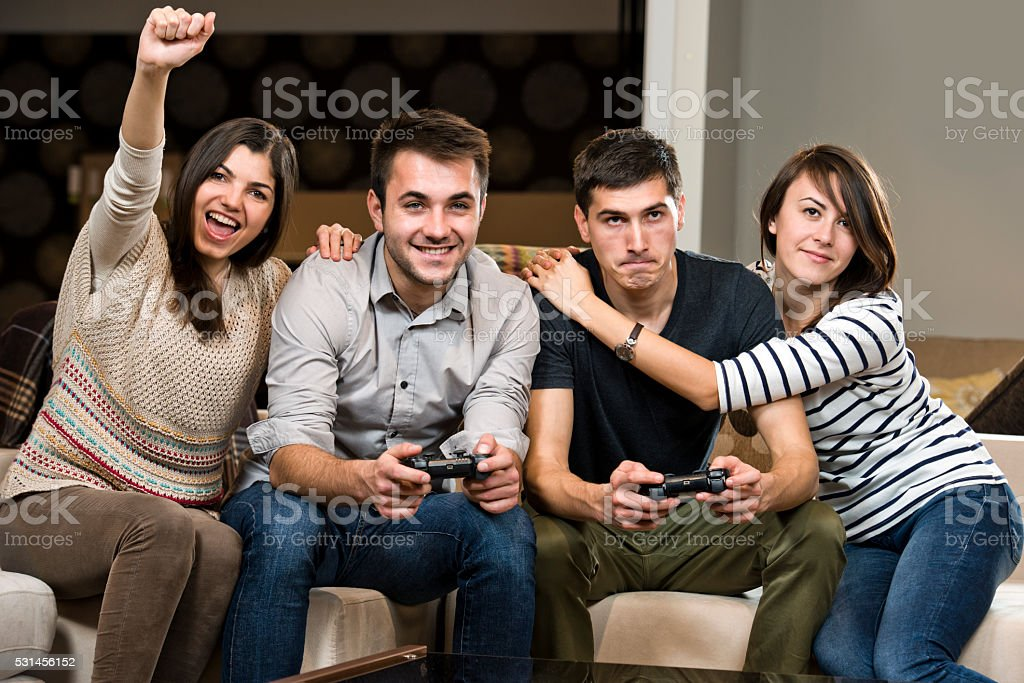 Two young friends playing console games. stock photo