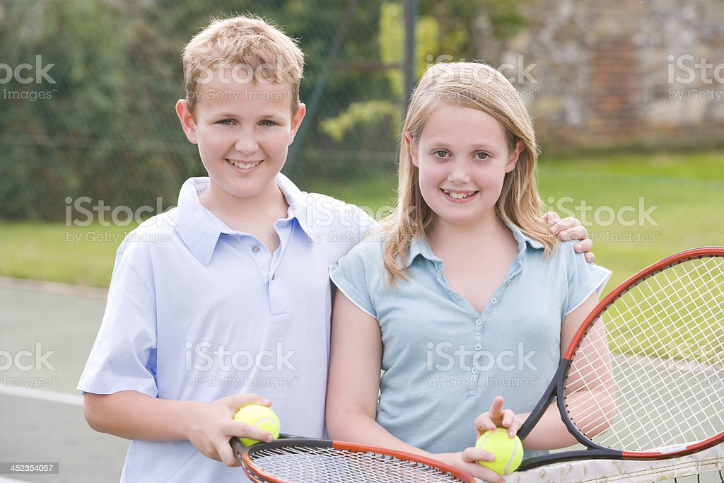 Two young friends with rackets on tennis court smiling royalty-free stock photo