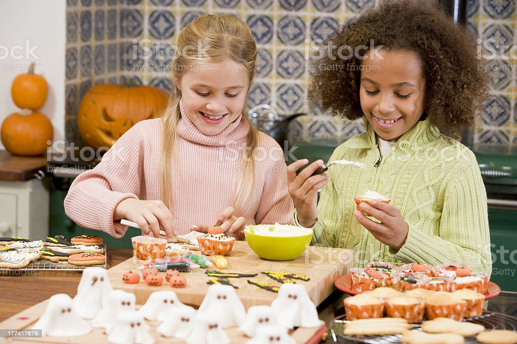 Two young girl friends at Halloween making treats and smiling stock photo