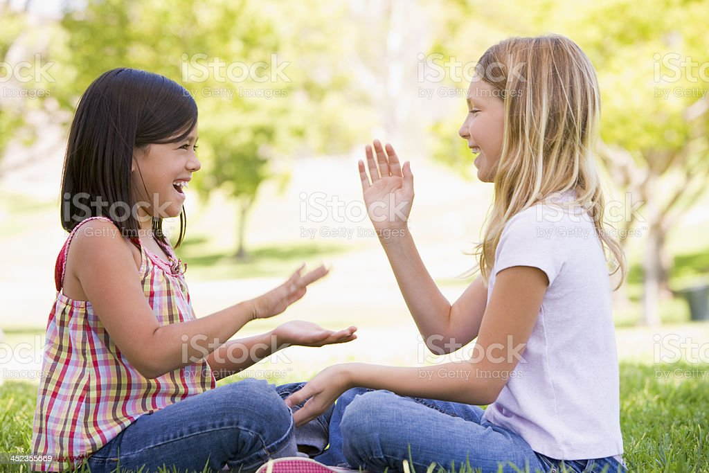 Two young girl friends sitting outdoors playing patty cake smiling stock photo