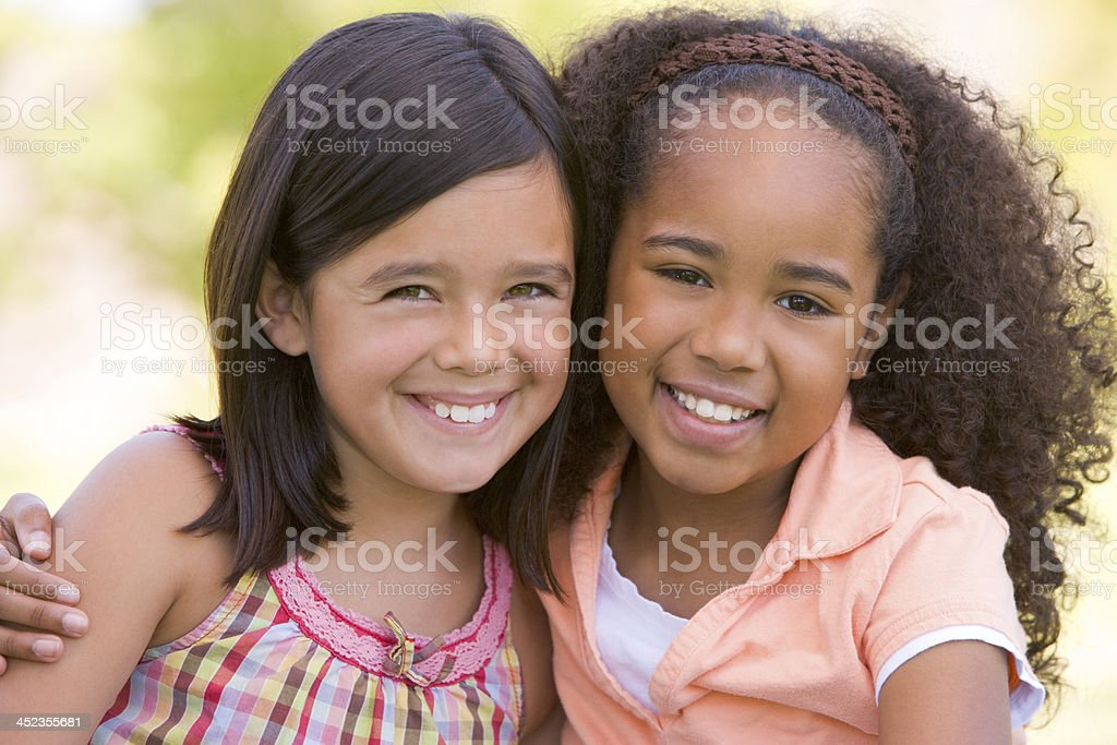 Two young girl friends sitting outdoors smiling royalty-free stock photo