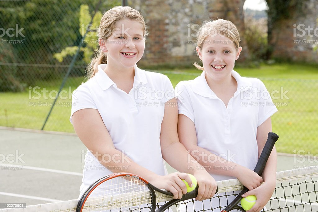 Two young girl friends with rackets on tennis court smiling royalty-free stock photo
