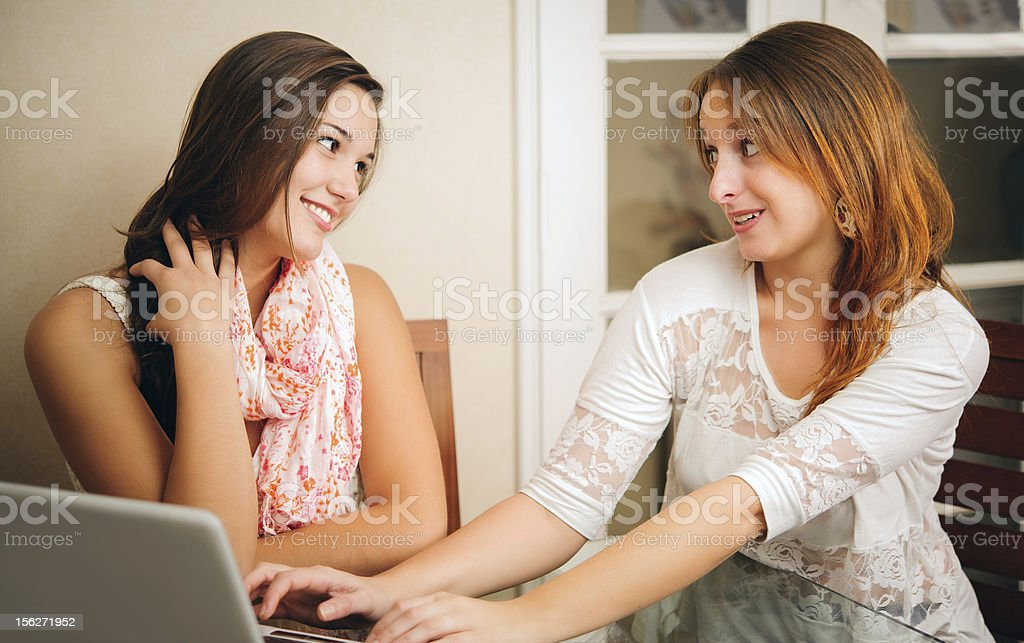 Two young girlfriends talking in front of computer royalty-free stock photo
