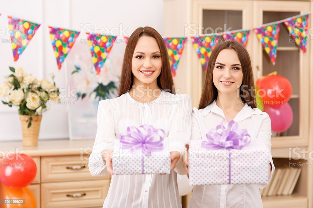 Two young girls are offering presents stock photo