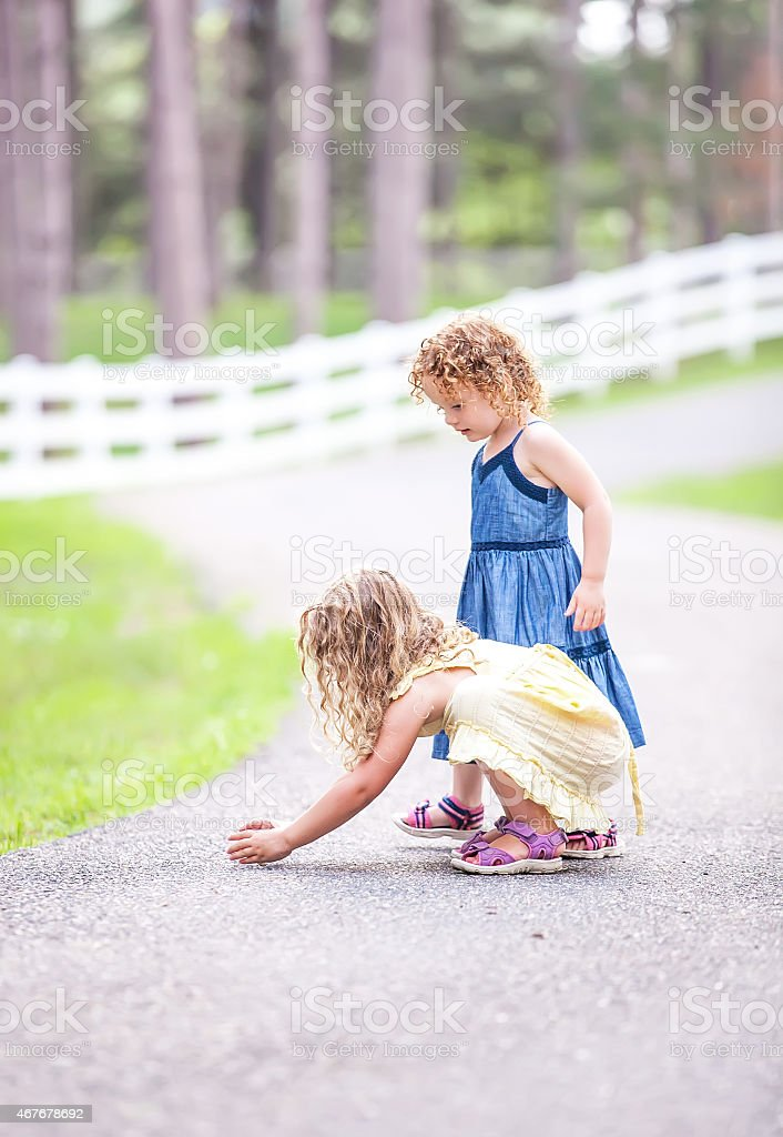 Two Young Girls Catching A Small Frog stock photo