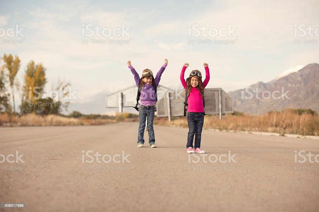 Two young girls dressed as pilots wearing jet packs stock photo