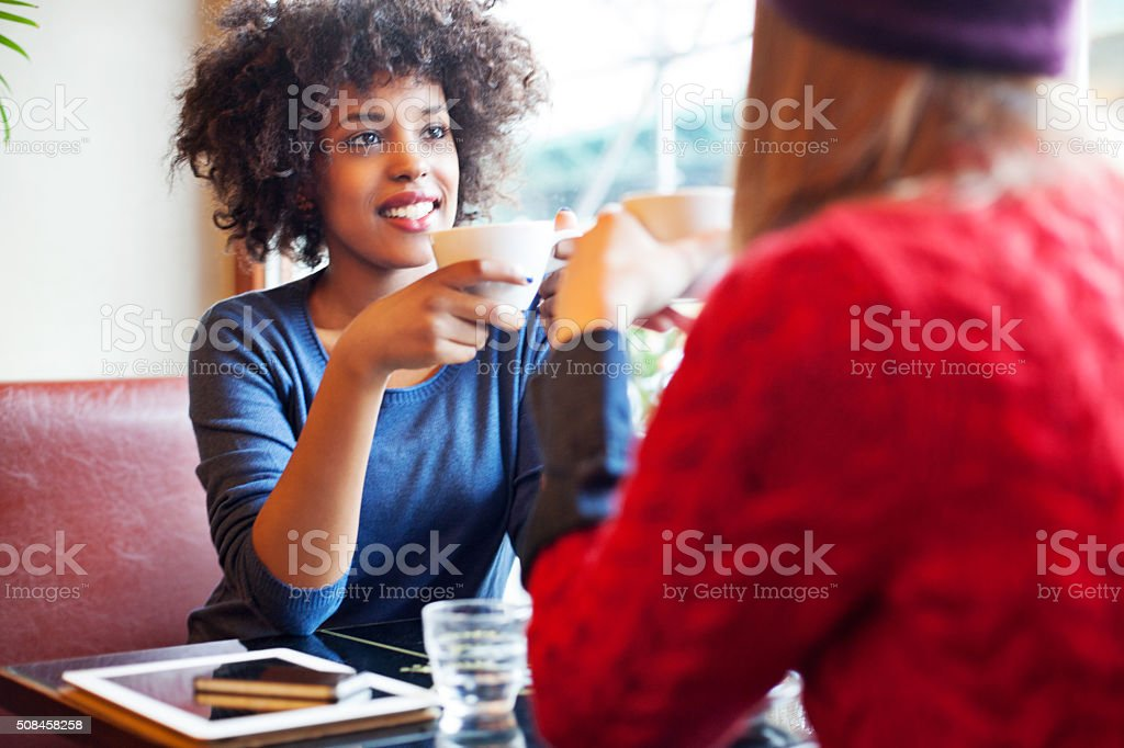 Two young girls drinking coffee together stock photo