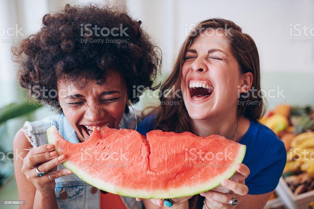 Two young girls enjoying a watermelon stock photo