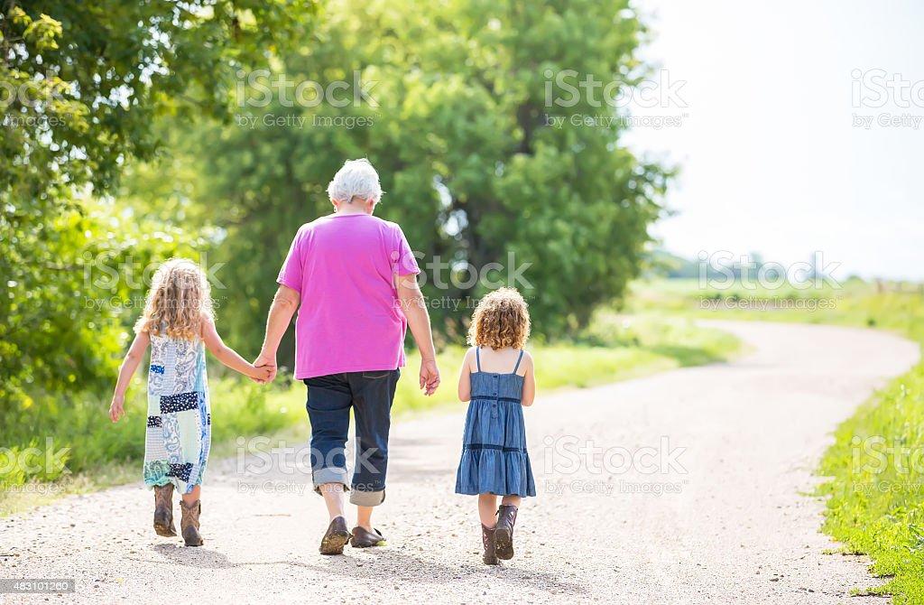 Two Young Girls & Grandma Walking Down Rural Driveway stock photo