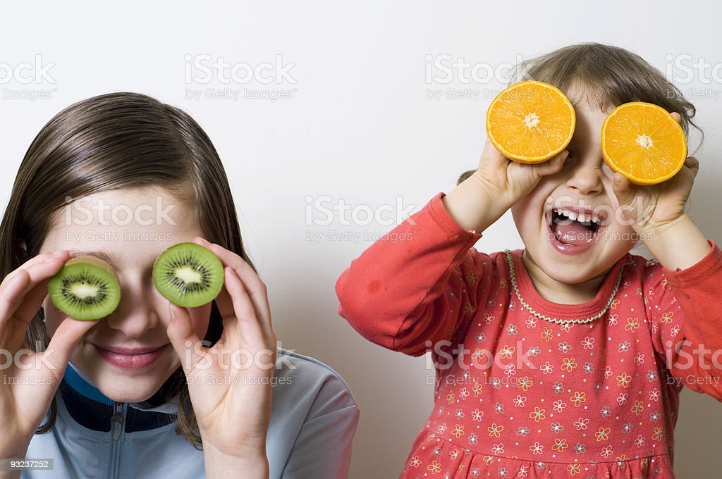 Two young girls holding sliced fruit to their eyes royalty-free stock photo