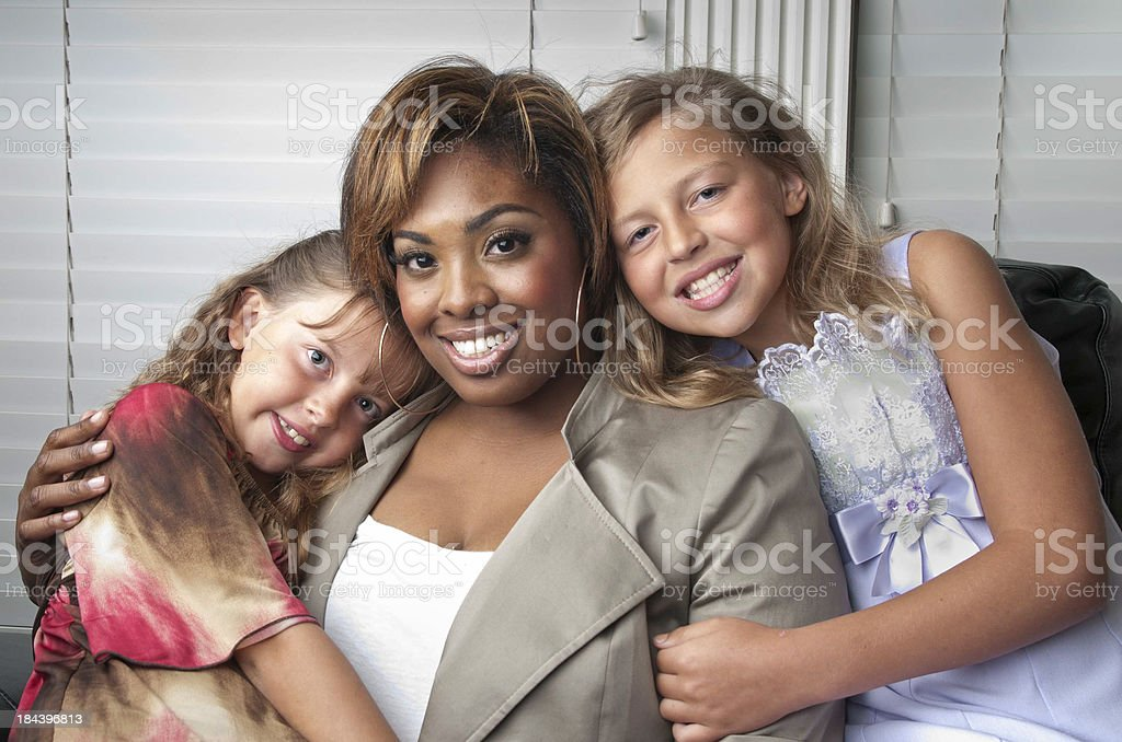 Two Young Girls Hug Family Friend stock photo